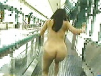 野外露出。人がぞろぞろ通る動く歩道で大胆に露出する女