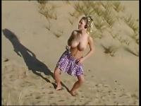 砂漠で露出! オッパイ丸出しで踊る美巨乳金髪娘!