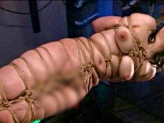 後手縛りで芋虫のように緊縛されたM女が麻縄から乳房がはみ出る程キツく縛...