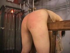拷問台に磔状態で拘束されるM女。お尻をむき出しにしたまま鞭でスパンキン...